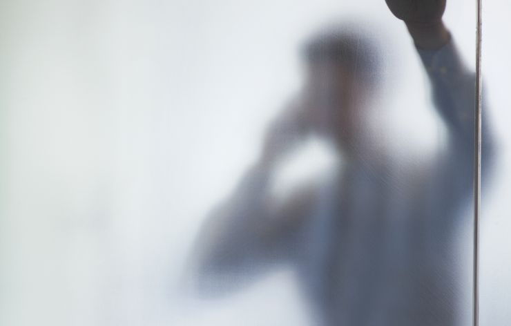 Man on phone behind white out film glass | Demers Glass AZ