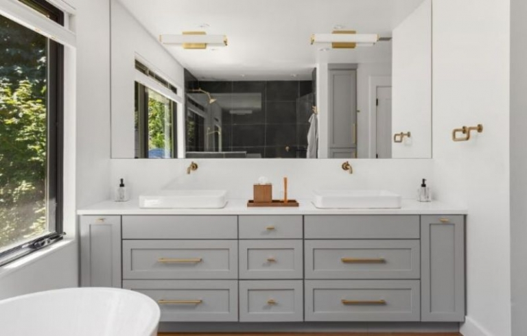 Remodeled bathroom with large mirror and modern vanity